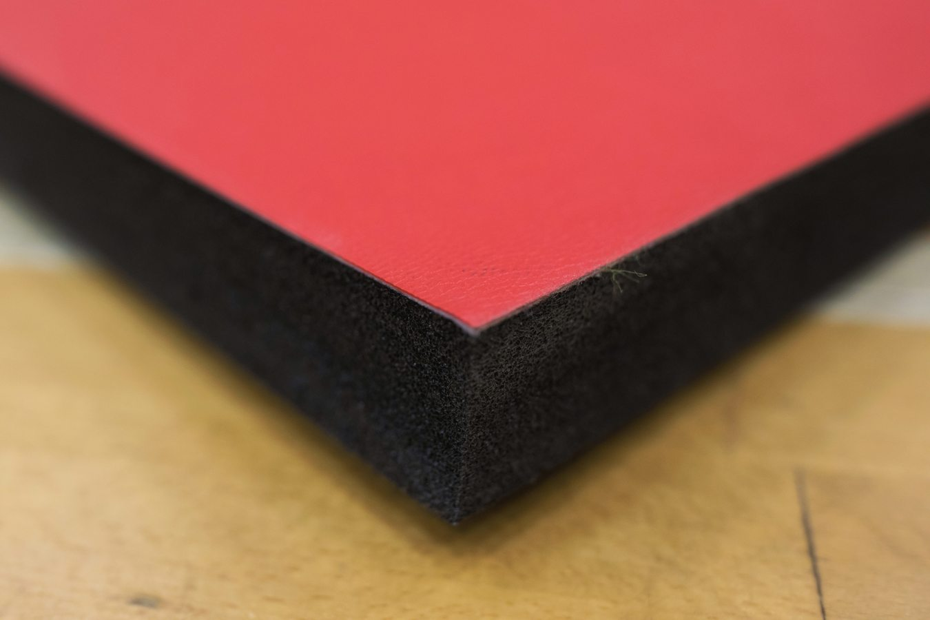 Corner of Red Promat PVC Smooth Roll Out Mats